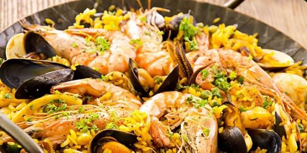 Paella z owocami morza podawana na pojedyńszej patelni do paelli
