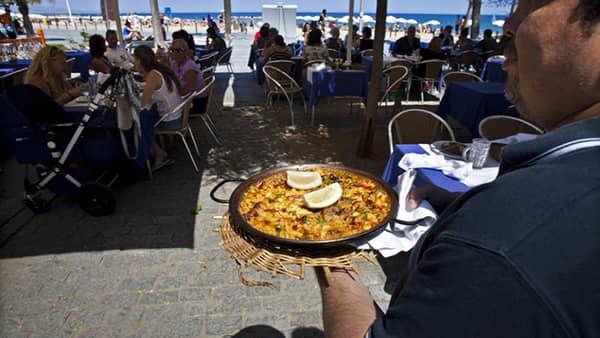 Kelner niosący paellę w barze na plaży na wybrzeżu śródziemnomorskim w Hiszpanii.