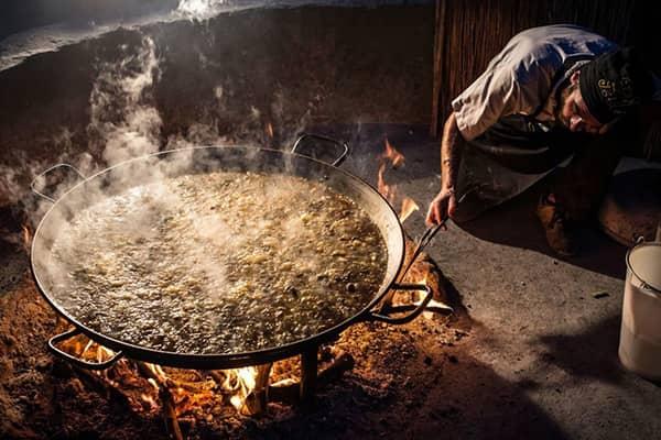 Szef kuchni sprawdzający ogień podczas gotowania paelli.
