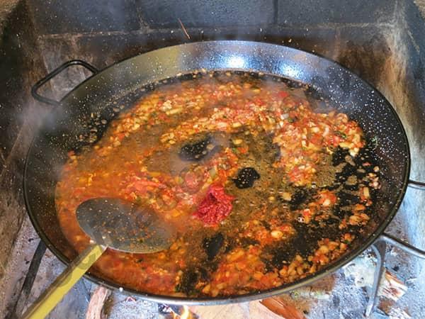 """Sofrito"" to oliwa z oliwek, czosnek, cebula i smażony pomidor na patelni do paelli"