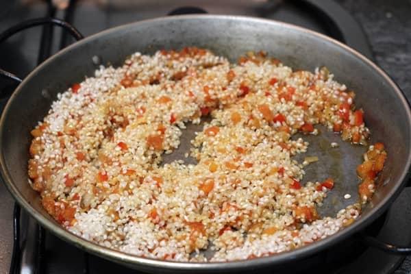 Smażenie ryżu podczas przygotowywania paelli.