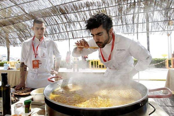 Kucharz degustujący bulion paelli, aby sprawdzić czy jest odpowiednio słony.