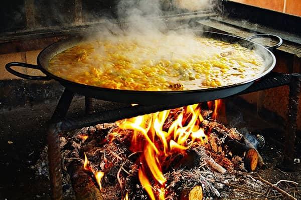 Paella przyrządzana na ogniu z drewna w czasie procesu gotowania.